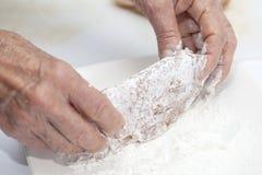 Πασπαλίζοντας μια UEBL κορδονιών με ψίχουλα - που προσθέτει το αλεύρι στοκ φωτογραφία