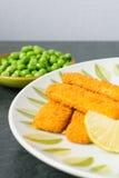 Πασπαλισμένα με ψίχουλα δάχτυλα ψαριών με τα μπιζέλια στοκ φωτογραφία με δικαίωμα ελεύθερης χρήσης