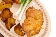 Πασπαλισμένη με ψίχουλα μπριζόλα που εξυπηρετείται με τις νέες πατάτες και τα νέα κρεμμύδια Στοκ εικόνες με δικαίωμα ελεύθερης χρήσης