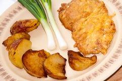 Πασπαλισμένη με ψίχουλα μπριζόλα που εξυπηρετείται με τις νέες πατάτες και τα νέα κρεμμύδια Στοκ Εικόνα