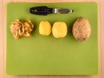 Πατάτες, δέρματα και peeler με το copyspace Στοκ Εικόνες