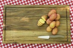 Πατάτες και μαχαίρι στο ξύλινο πιάτο Στοκ εικόνες με δικαίωμα ελεύθερης χρήσης