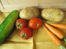 Πατάτες, πορτοκαλιά καρότα, κολοκύθια και κόκκινες φρέσκες ντομάτες στο κίτρινο τραπεζομάντιλο Στοκ Εικόνα