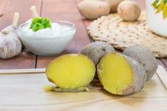 Πατάτες σακακιών περικοπών στην ξύλινη μαγειρεύοντας σανίδα Στοκ Εικόνες