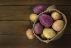Πατάτες συγκομιδών burlap στο σάκο στο ξύλινο υπόβαθρο Στοκ εικόνες με δικαίωμα ελεύθερης χρήσης