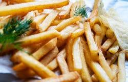 Πατάτες τηγανιτών πατατών με τα κλαδάκια άνηθου σε ένα άσπρο φύλλο του εγγράφου Στοκ Φωτογραφίες