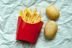 Πατάτες τηγανιτών πατατών σε κόκκινη τσάντα εγγράφου και δύο πατάτες Στοκ Φωτογραφίες