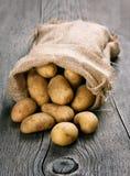 Πατάτες burlap στο σάκο στο ξύλινο υπόβαθρο Στοκ Εικόνα