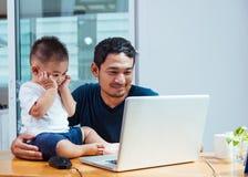 Πατέρας ατόμων που εργάζεται στο φορητό προσωπικό υπολογιστή στοκ φωτογραφία