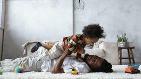 Πατέρας αφροαμερικάνων που ανυψώνει το μικτό γιο φυλών επάνω απόθεμα βίντεο