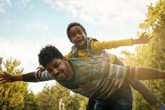 Πατέρας αφροαμερικάνων που κρατά την κόρη της στο shoulde στοκ εικόνες