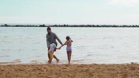 Πατέρας, γιος και κόρη που έχουν τη διασκέδαση μαζί, χορός και άλμα νεολαίες ενηλίκων απόθεμα βίντεο