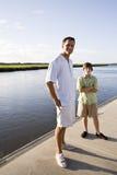 Πατέρας και έφηβος γιος που στέκονται στην αποβάθρα από το ύδωρ στοκ φωτογραφία με δικαίωμα ελεύθερης χρήσης