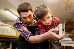 Πατέρας και λίγος γιος με την ξύλινη σανίδα στο εργαστήριο Στοκ εικόνες με δικαίωμα ελεύθερης χρήσης