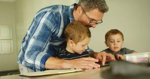 Πατέρας και αμφιθαλείς που χρησιμοποιούν την ψηφιακή ταμπλέτα στο καθιστικό 4k απόθεμα βίντεο