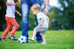 Πατέρας και γιοι που παίζουν το ποδόσφαιρο στο πάρκο Στοκ φωτογραφίες με δικαίωμα ελεύθερης χρήσης