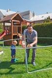Πατέρας και γιος κατά το εγκατάσταση των μεγάλων τραμπολίνων κήπων Στοκ φωτογραφίες με δικαίωμα ελεύθερης χρήσης