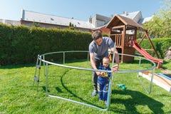 Πατέρας και γιος κατά το εγκατάσταση των μεγάλων τραμπολίνων κήπων Στοκ φωτογραφία με δικαίωμα ελεύθερης χρήσης
