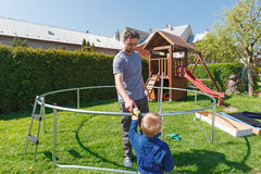Πατέρας και γιος κατά το εγκατάσταση των μεγάλων τραμπολίνων κήπων Στοκ εικόνες με δικαίωμα ελεύθερης χρήσης