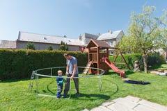 Πατέρας και γιος κατά το εγκατάσταση των μεγάλων τραμπολίνων κήπων Στοκ Εικόνες