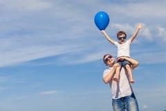 Πατέρας και γιος με το μπλε παιχνίδι μπαλονιών στην παραλία στην ημέρα Στοκ Φωτογραφίες