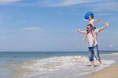 Πατέρας και γιος με το μπλε παιχνίδι μπαλονιών στην παραλία στην ημέρα Στοκ εικόνες με δικαίωμα ελεύθερης χρήσης