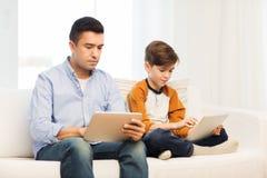 Πατέρας και γιος με το PC ταμπλετών στο σπίτι Στοκ φωτογραφία με δικαίωμα ελεύθερης χρήσης