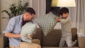 Πατέρας και γιος που έχουν την πάλη μαξιλαριών στο σπίτι φιλμ μικρού μήκους