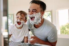 Πατέρας και γιος που έχουν τη διασκέδαση ξυρίζοντας στο λουτρό Στοκ φωτογραφίες με δικαίωμα ελεύθερης χρήσης
