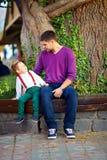Πατέρας και γιος που έχουν τη διασκέδαση στον πάγκο στο πάρκο Στοκ Εικόνες