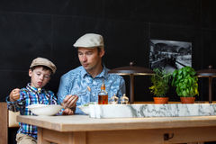 Πατέρας και γιος που έχουν το μεσημεριανό γεύμα από κοινού Στοκ Εικόνες