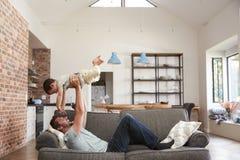 Πατέρας και γιος που έχουν το παιχνίδι διασκέδασης στον καναπέ από κοινού στοκ φωτογραφία