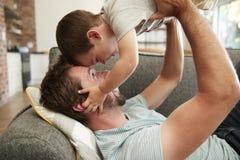 Πατέρας και γιος που έχουν το παιχνίδι διασκέδασης στον καναπέ από κοινού στοκ φωτογραφίες με δικαίωμα ελεύθερης χρήσης
