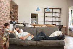 Πατέρας και γιος που έχουν το παιχνίδι διασκέδασης στον καναπέ από κοινού στοκ φωτογραφία με δικαίωμα ελεύθερης χρήσης