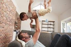Πατέρας και γιος που έχουν το παιχνίδι διασκέδασης στον καναπέ από κοινού στοκ εικόνα με δικαίωμα ελεύθερης χρήσης
