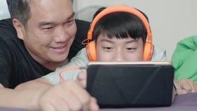Πατέρας και γιος που απολαμβάνουν έναν κινηματογράφο στον υπολογιστή ταμπλετών με το πρόσωπο χαμόγελου στο σπίτι απόθεμα βίντεο