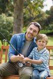 Πατέρας και γιος που αλιεύουν στον πάγκο πάρκων Στοκ Φωτογραφίες