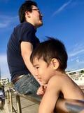 Πατέρας και γιος που εξετάζουν τη αντίθετη πλευρά του ωκεανού στοκ εικόνα με δικαίωμα ελεύθερης χρήσης