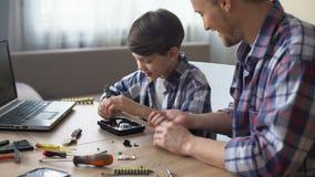 Πατέρας και γιος που επισκευάζουν τις μικρή οικιακές συσκευές, την υποστήριξη και την εμπιστοσύνη απόθεμα βίντεο