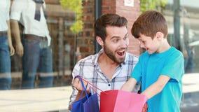 Πατέρας και γιος που κοιτάζουν στην τσάντα αγορών απόθεμα βίντεο