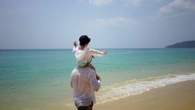 Πατέρας και γιος που περπατούν με τα πόδια κατά μήκος της παραλίας κοντά στον ωκεανό απόθεμα βίντεο
