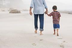Πατέρας και γιος που περπατούν στην άμμο στην παραλία στοκ φωτογραφία
