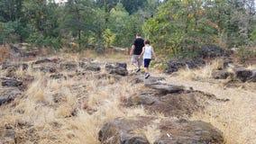 Πατέρας και γιος που περπατούν στους βράχους και τις καφετιές χλόες στοκ φωτογραφία με δικαίωμα ελεύθερης χρήσης