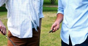 Πατέρας και γιος που προετοιμάζουν τα τρόφιμα στη σχάρα και που αλληλεπιδρούν ο ένας με τον άλλον στο πάρκο απόθεμα βίντεο