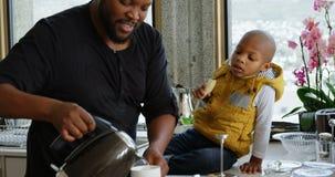 Πατέρας και γιος που προετοιμάζουν τον καφέ στην κουζίνα 4k απόθεμα βίντεο