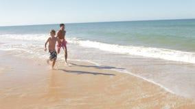 Πατέρας και γιος που τρέχουν κατά μήκος της ακτής φιλμ μικρού μήκους