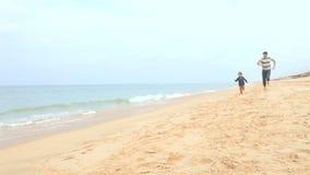 Πατέρας και γιος που τρέχουν κατά μήκος της παραλίας από κοινού απόθεμα βίντεο