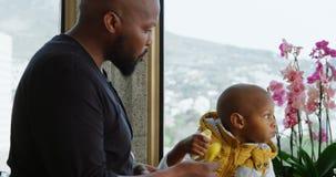 Πατέρας και γιος που τρώνε την μπανάνα στην κουζίνα στο σπίτι 4k απόθεμα βίντεο