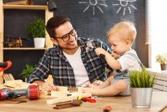 Πατέρας και γιος που χαράζονται του ξύλου στο εργαστήριο ξυλουργικής στοκ εικόνα με δικαίωμα ελεύθερης χρήσης