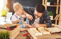 Πατέρας και γιος που χαράζονται του ξύλου στο εργαστήριο ξυλουργικής στοκ φωτογραφία με δικαίωμα ελεύθερης χρήσης